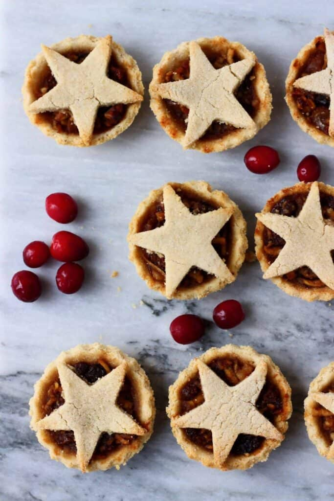 Six mince pies topped with stars against a marble background scattered with fresh red cranberries