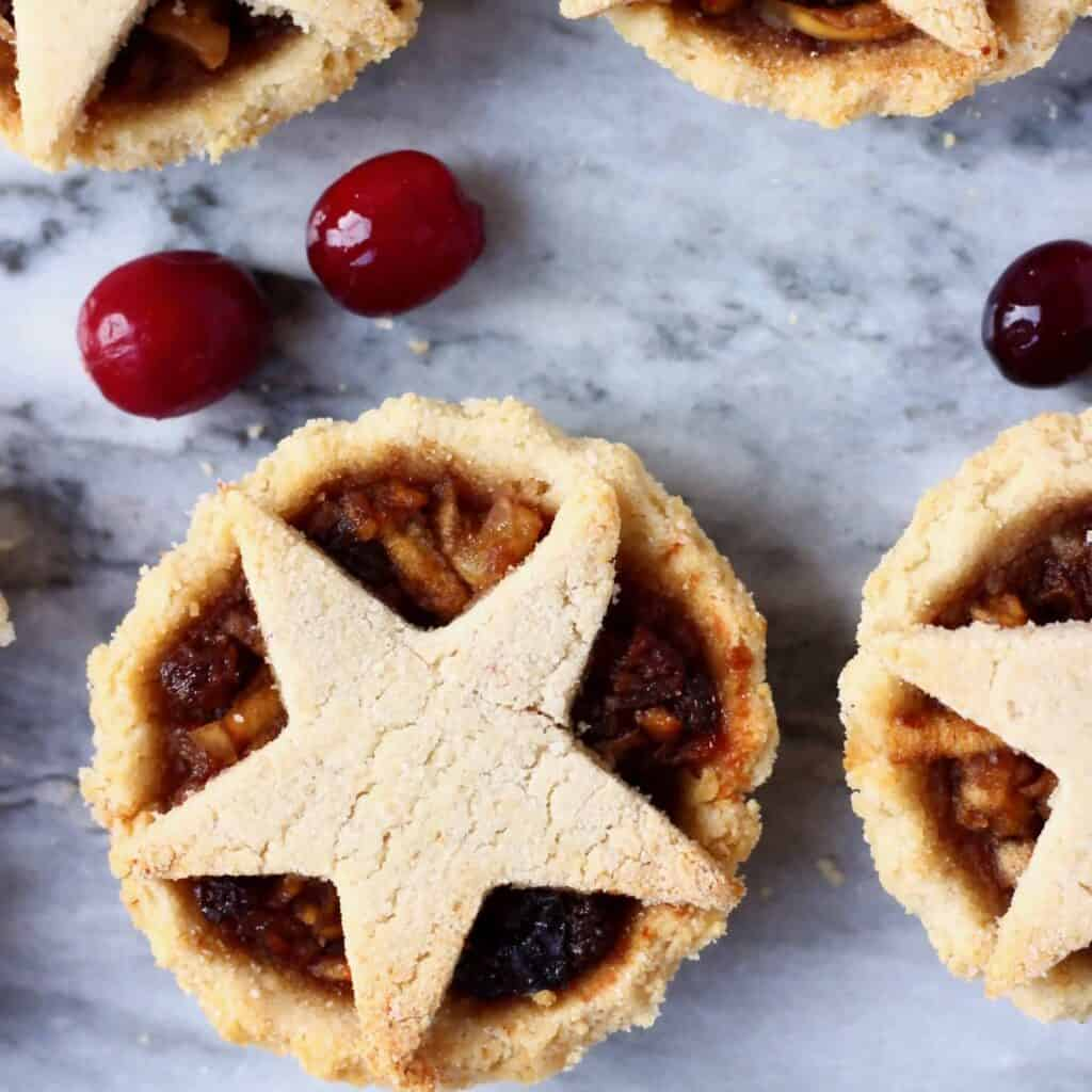 Photo of three mince pies topped with pastry stars against a marble background scattered with fresh cranberries
