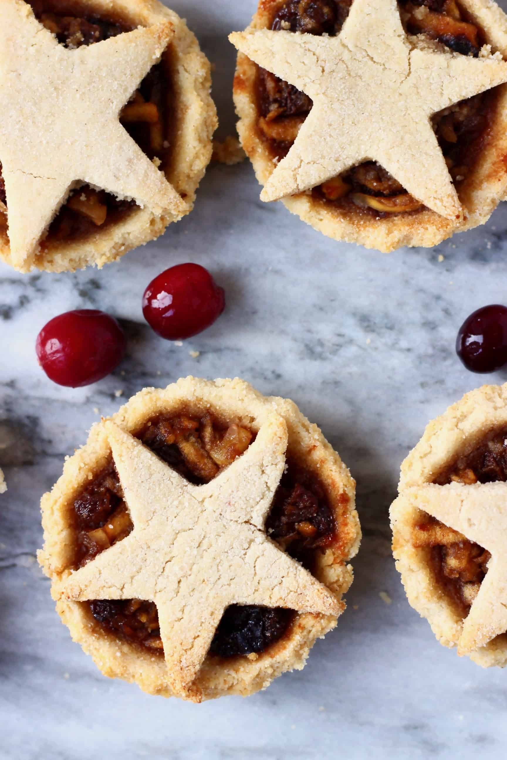 Four gluten-free vegan mince pies topped with pastry stars against a marble background