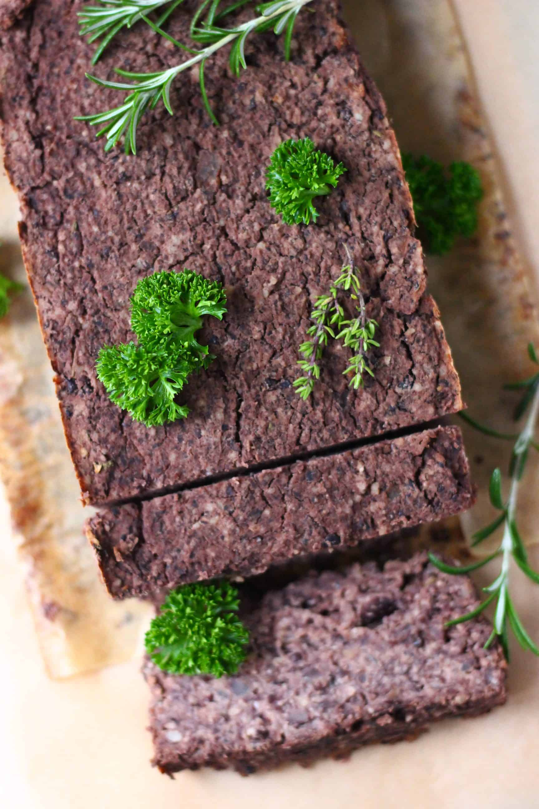 A black vegan meatloaf with two slices taken from it on a sheet of brown baking paper scattered with fresh green herbs