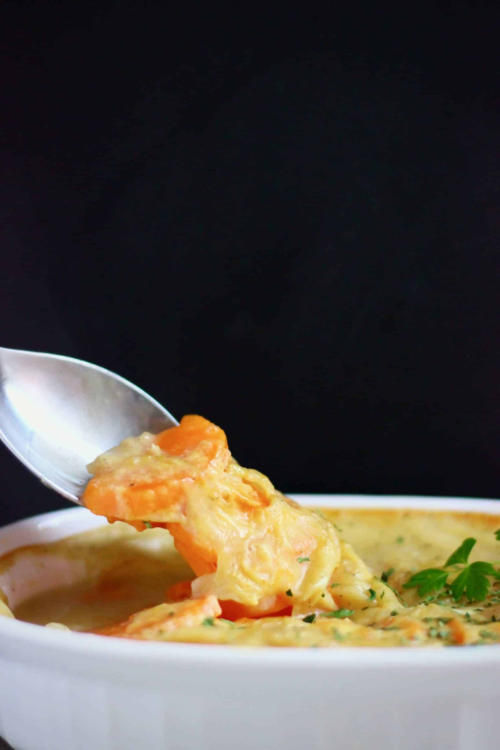 Vegan scalloped sweet potatoes in a white pie dish with a silver spoon lifting up a mouthful