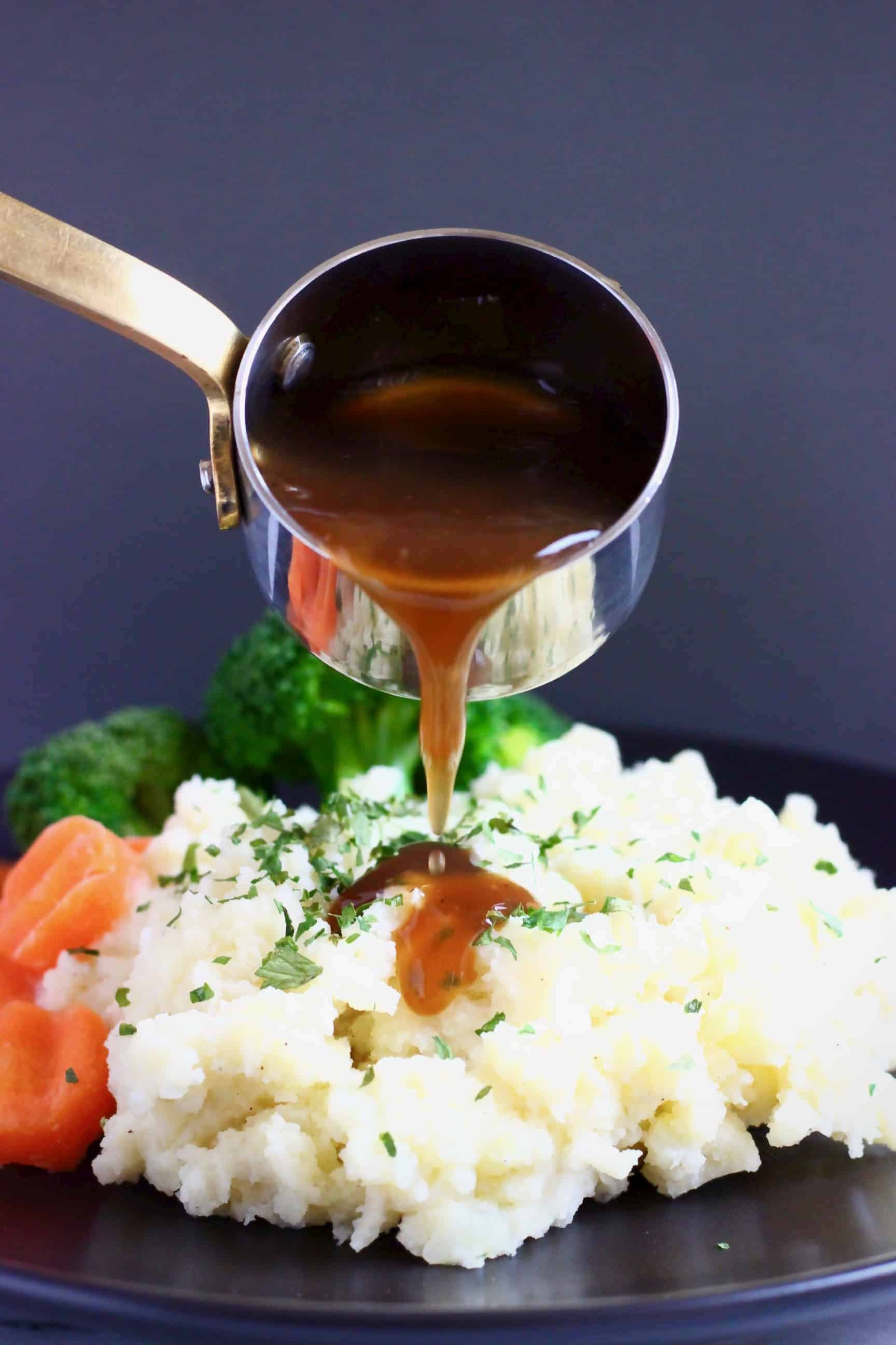 A pile of mashed potatoes topped with green herbs with sliced carrots and broccoli on a black plate with brown gravy being poured over in a silver saucepan