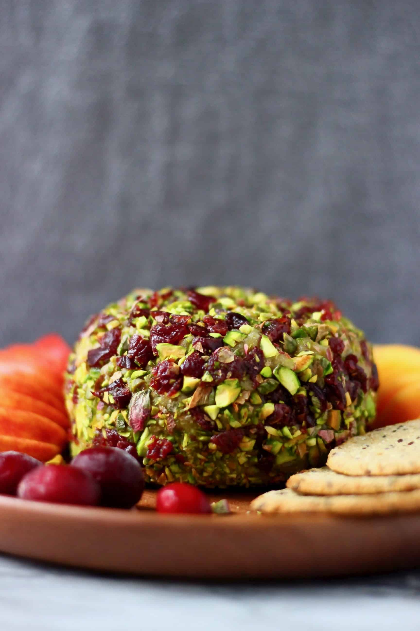 A ball of cashew cheese covered with chopped pistachios and dried cranberries on a wooden plate with sliced apples, oatcakes and fresh cranberries against a grey background