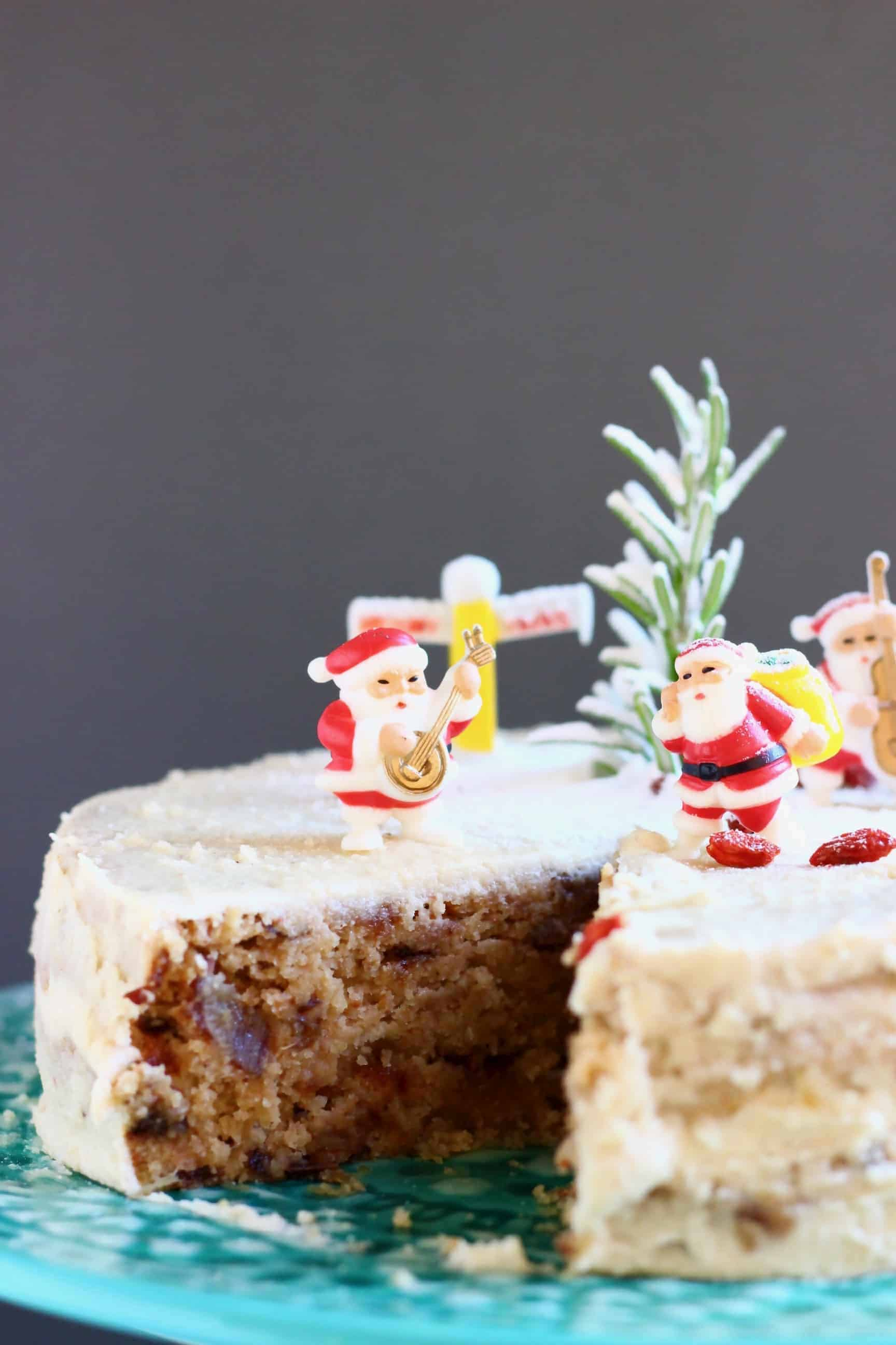 A Christmas fruit cake covered in white buttercream with a slice taken out of it topped with plastic santas against a grey background