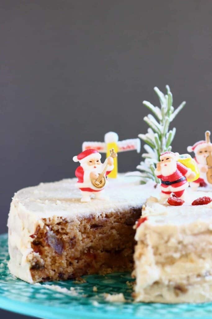 A fruit cake covered in white buttercream with a slice taken out of it topped with plastic santas against a grey background