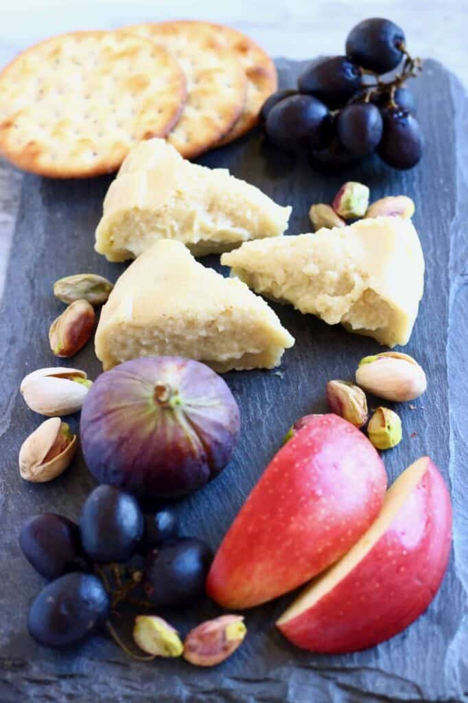 Photo of three triangular slices of brie on a black slab with sliced apples, grapes, figs, pistachios and crackers