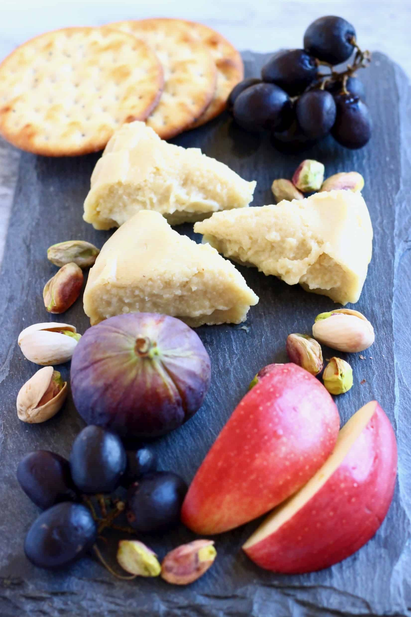 Three triangular slices of brie on a black slab with sliced apples, grapes, figs, pistachios and crackers