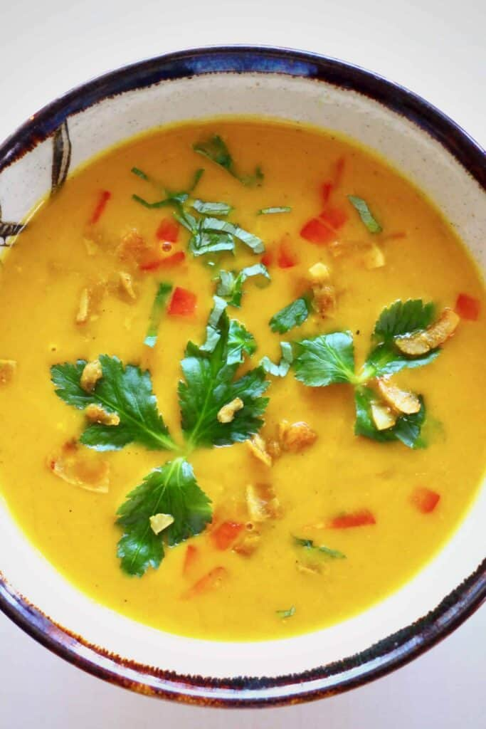 Photo of orange soup topped with coconut flakes, red peppers and green herbs in a white bowl with a dark brown rim