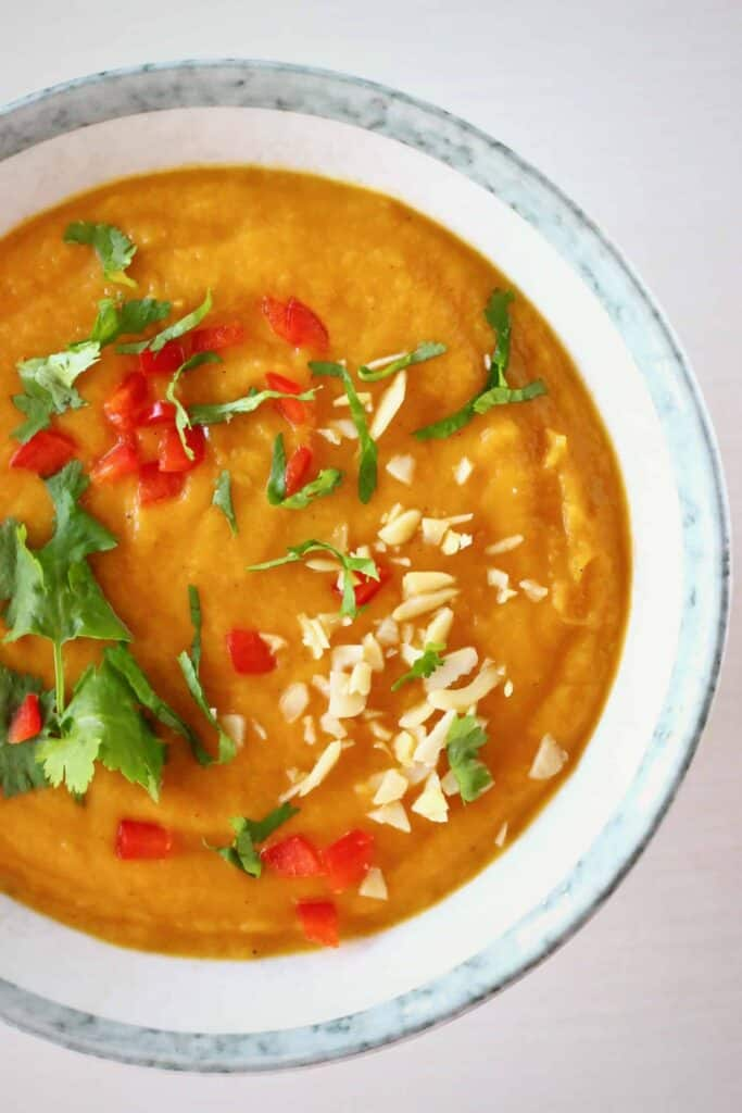 Photo of orange soup topped with green herbs, red peppers and chopped peanuts in a grey bowl against a white background