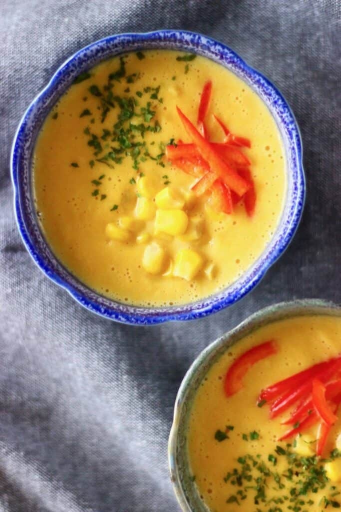 Photo of two bowls of yellow soup topped with yellow sweetcorn and red peppers and green herbs against a grey fabric background