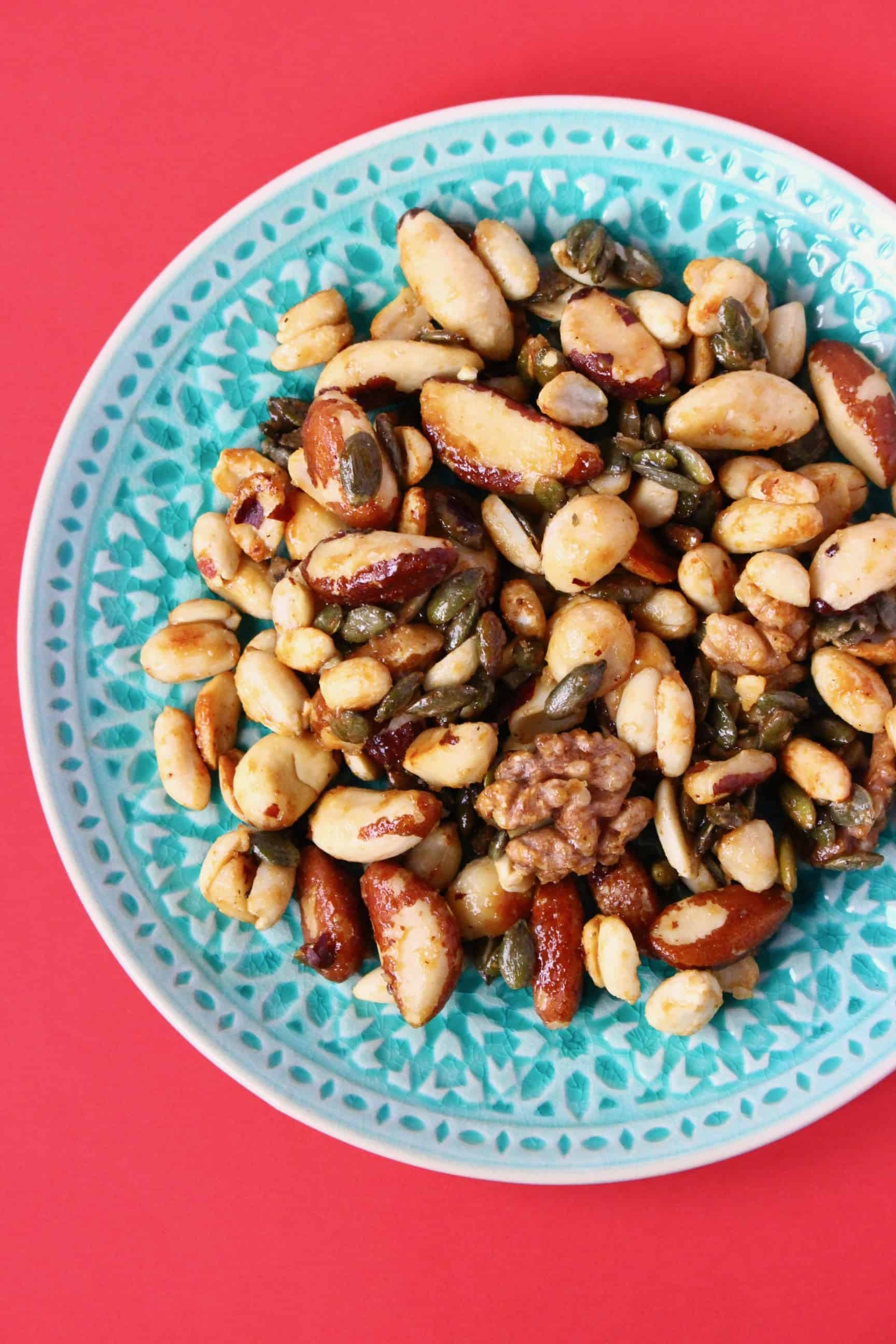 A pile of brown candied nuts on a green plate against a red background