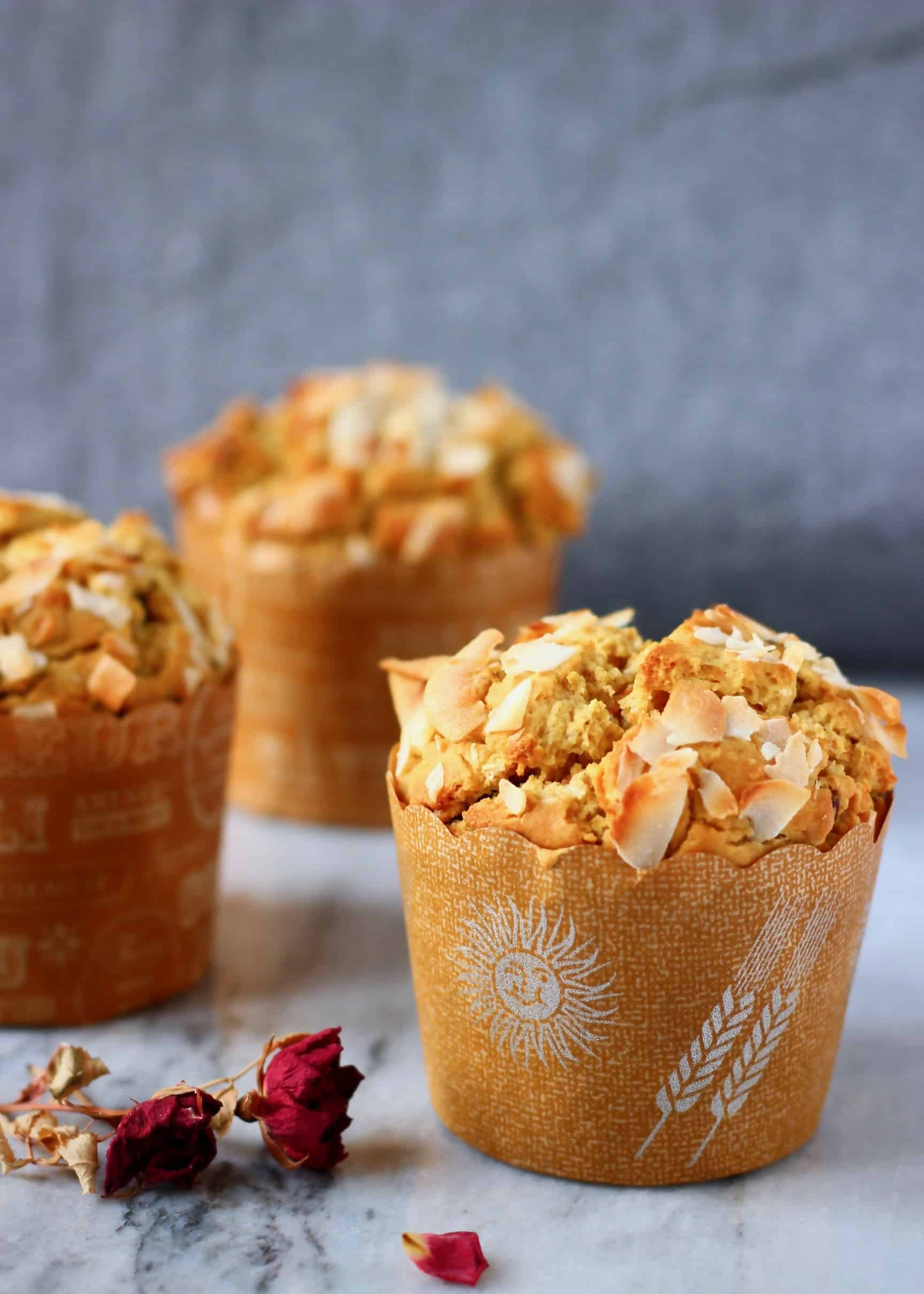 Three carrot muffins topped with coconut flakes on a marble slab decorated with dried roses against a grey fabric background