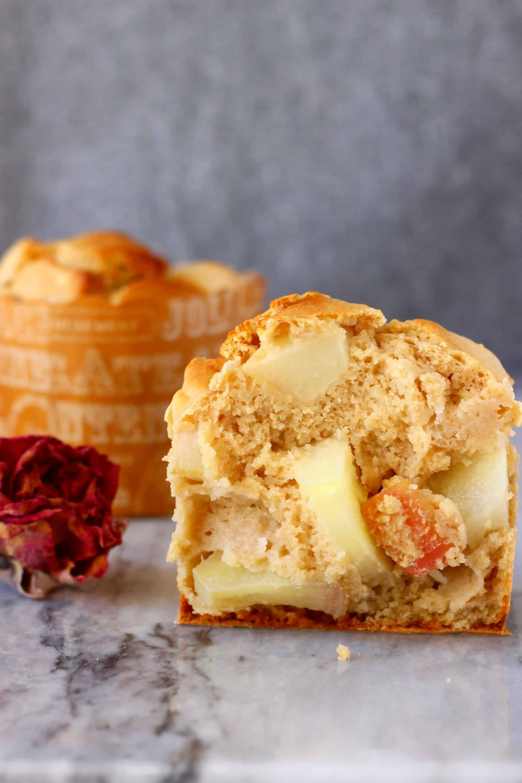Half a muffin with apples and another muffin on a marble slab against a grey background