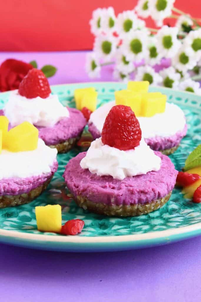Photo of four purple cheesecakes topped with whipped cream and fruit on a green plate abasing a purple background