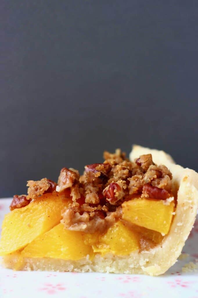 Photo of a slice of peach pie topped with brown crumble topping on a white plate against a dark grey background