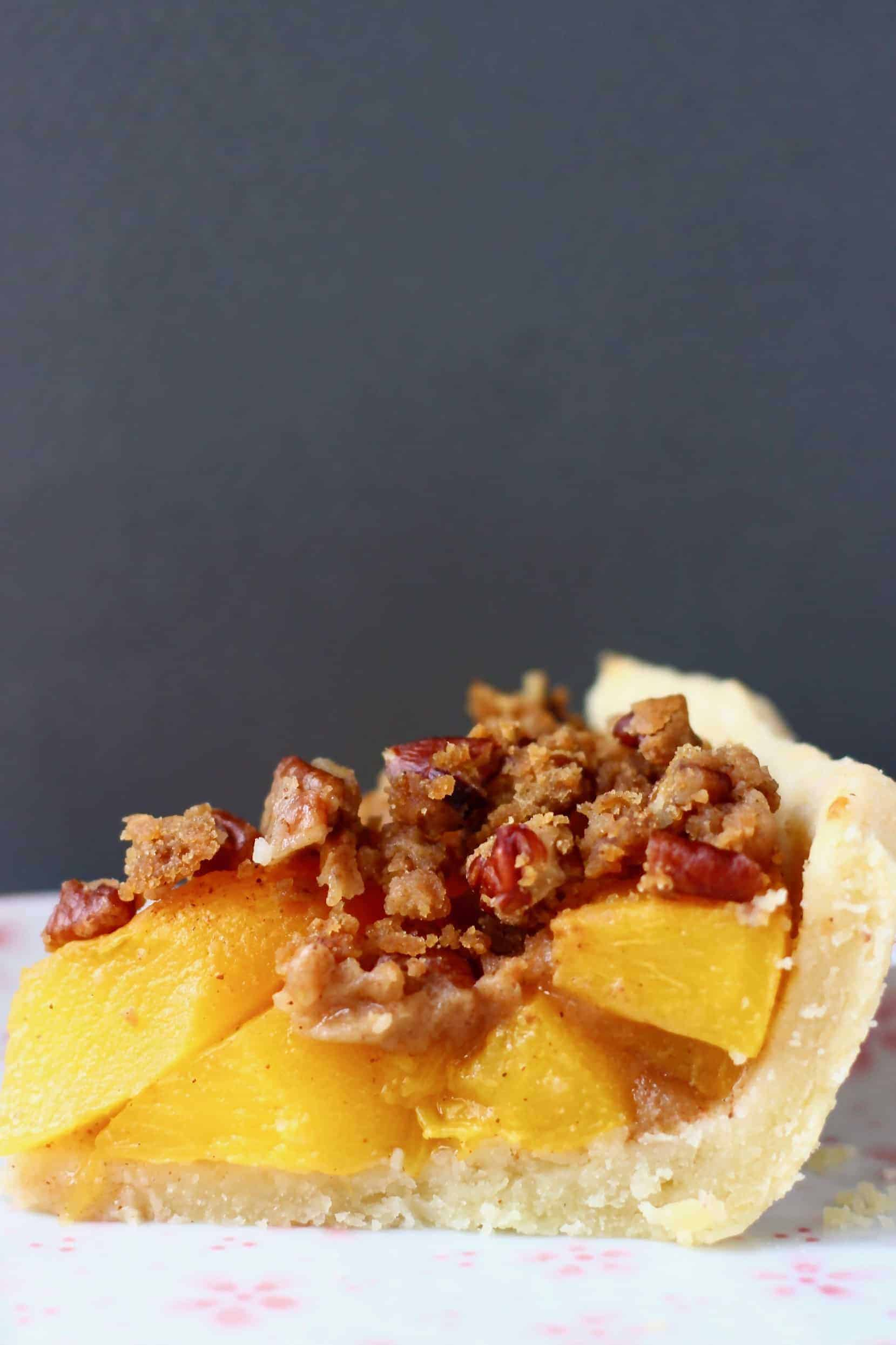 A slice of vegan peach pie topped with brown crumble topping on a white plate