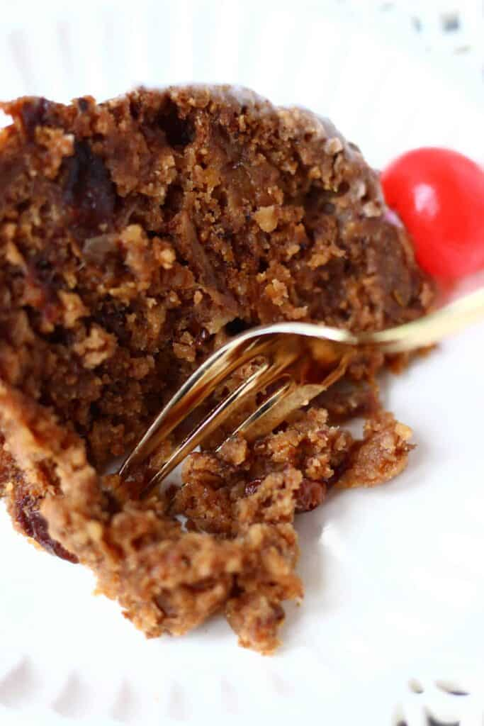 Photo of a slice of Christmas pudding topped with a bright red cherry on a white plate with a mouthful being taken with a gold fork
