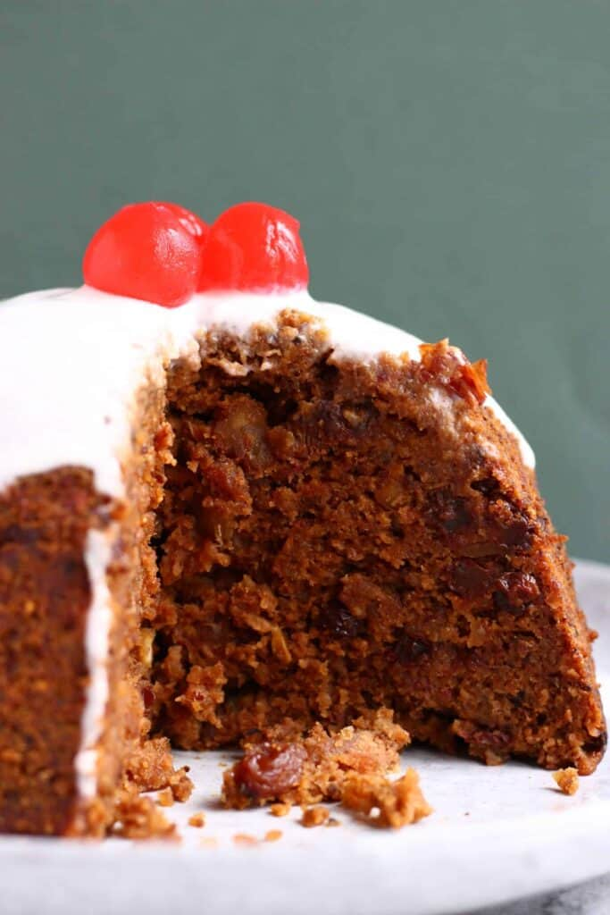 Photo of a round Christmas pudding with white cream poured over it topped with three bright red cherries against a dark green background