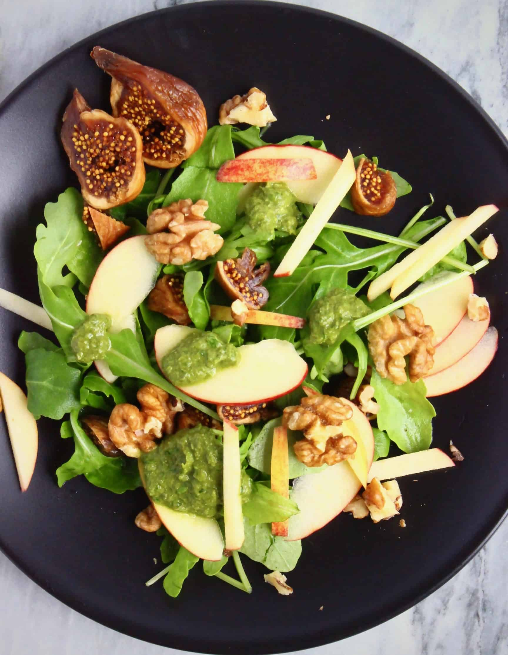 Apple slices, chopped dried figs, rocket and walnuts covered in a green pesto dressing on a black plate against a marble background