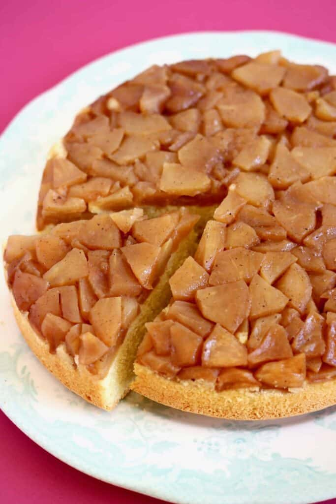 Photo of sponge cake topped with brown diced apples on a white plate against a bright pink background