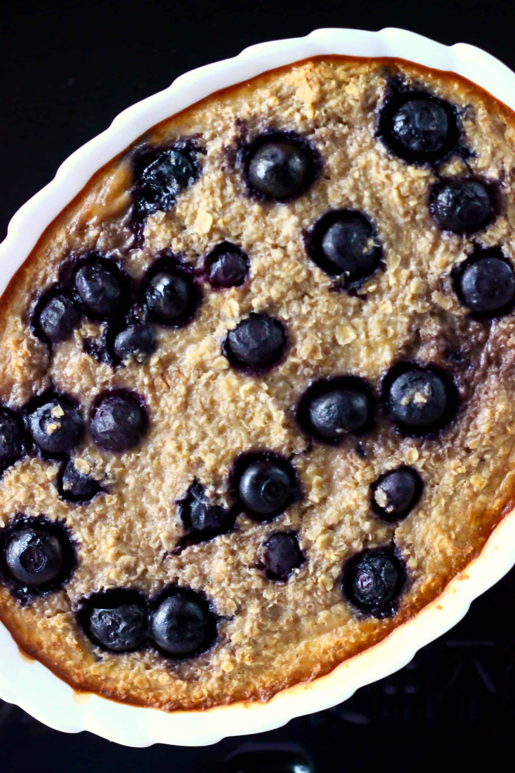 Baked oatmeal with blueberries in a white oval dish against a black background