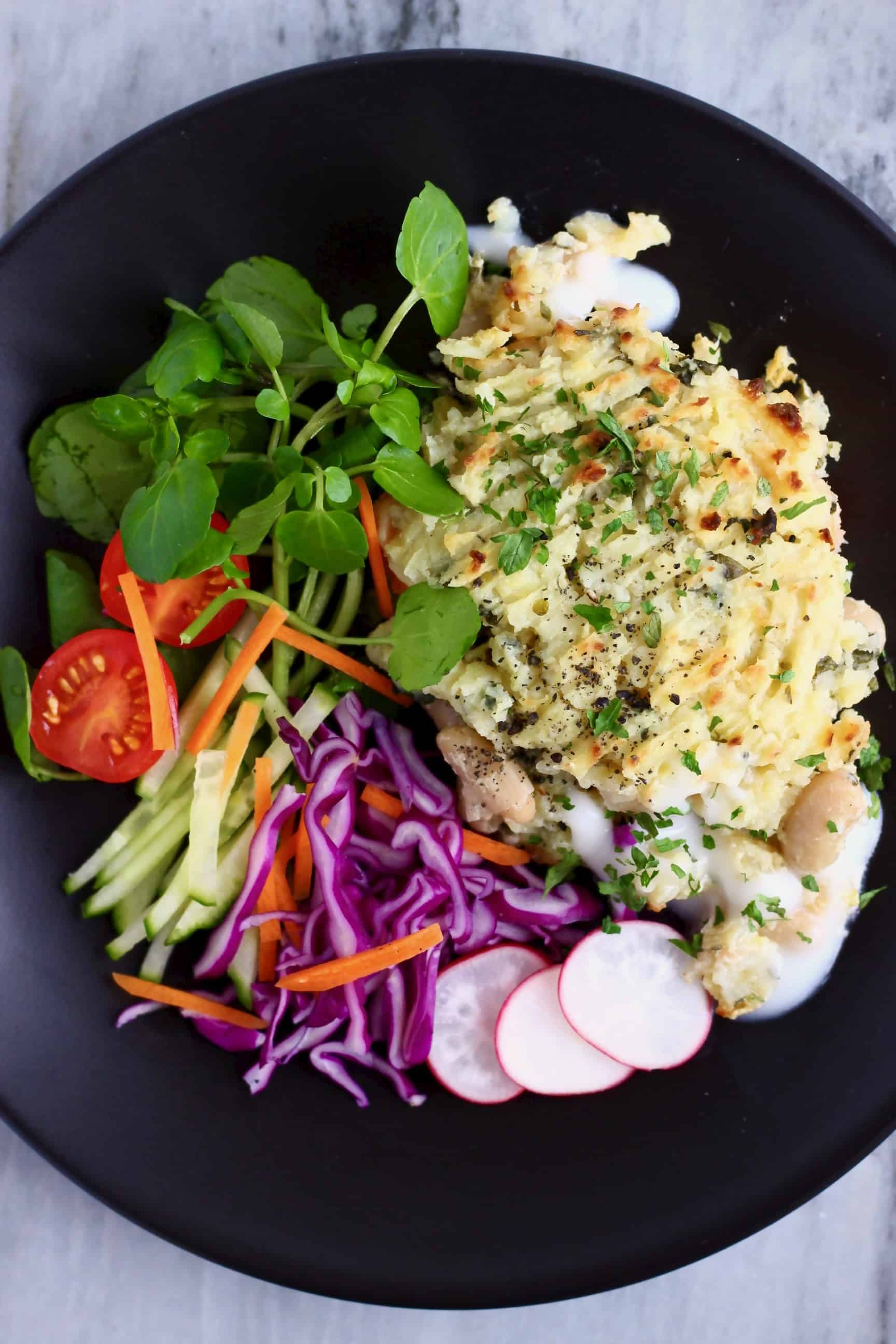 Vegan fish pie with watercress, sliced radishes and shredded purple cabbage on a black plate