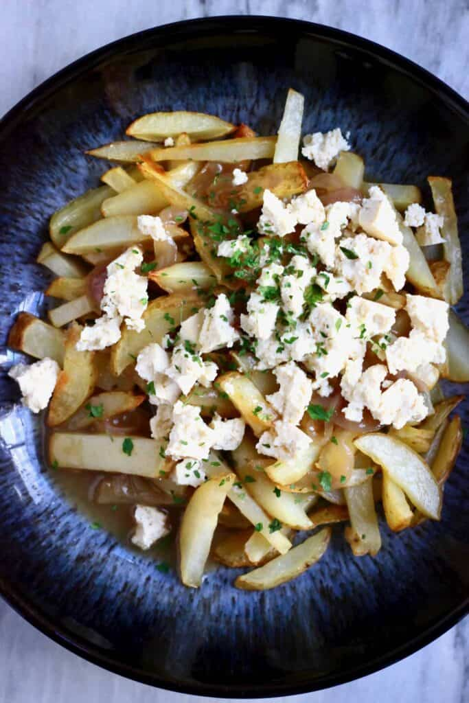 Photo of potato fries topped with crumbled up tofu, green herbs and brown gravy in a dark blue bowl