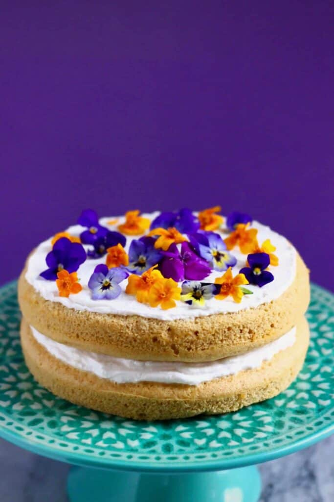 Photo of a pumpkin sponge sandwiched with white frosting topped with purple and orange flowers on a green cake stand against a purple background
