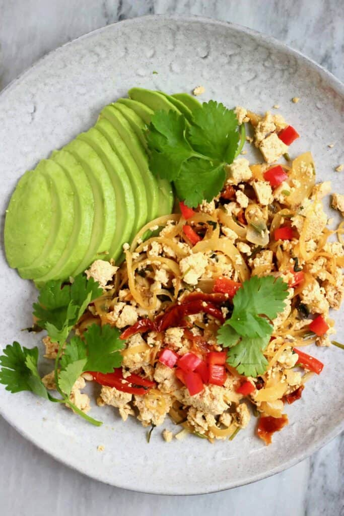 Photo of scrambled tofu with red peppers and a sliced avocado on a grey plate against a marble background