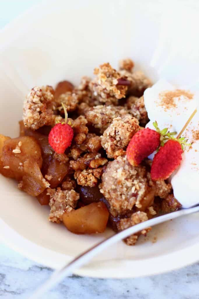 Photo of a portion of apple crumble and coconut yogurt in a white bowl topped with mini strawberries with a small silver spoon