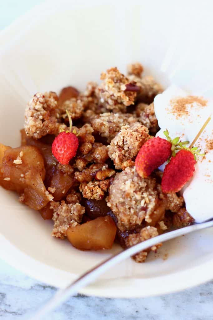 Photo of a portion of apple crumble and coconut yogurt in a white bowl topped with mini strawberries