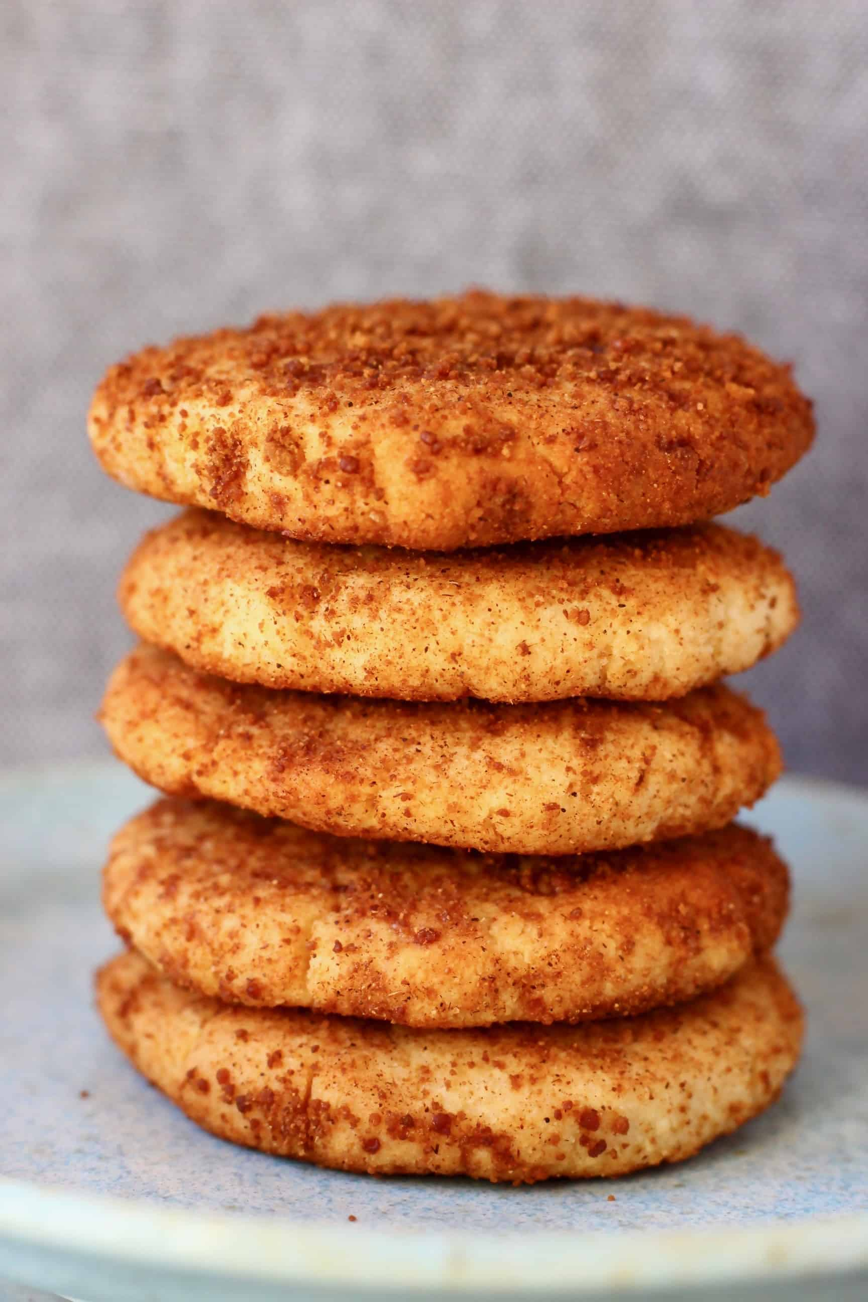 Five cookies coated in brown cinnamon sugar stacked on top of each other on a light blue plate against a grey background