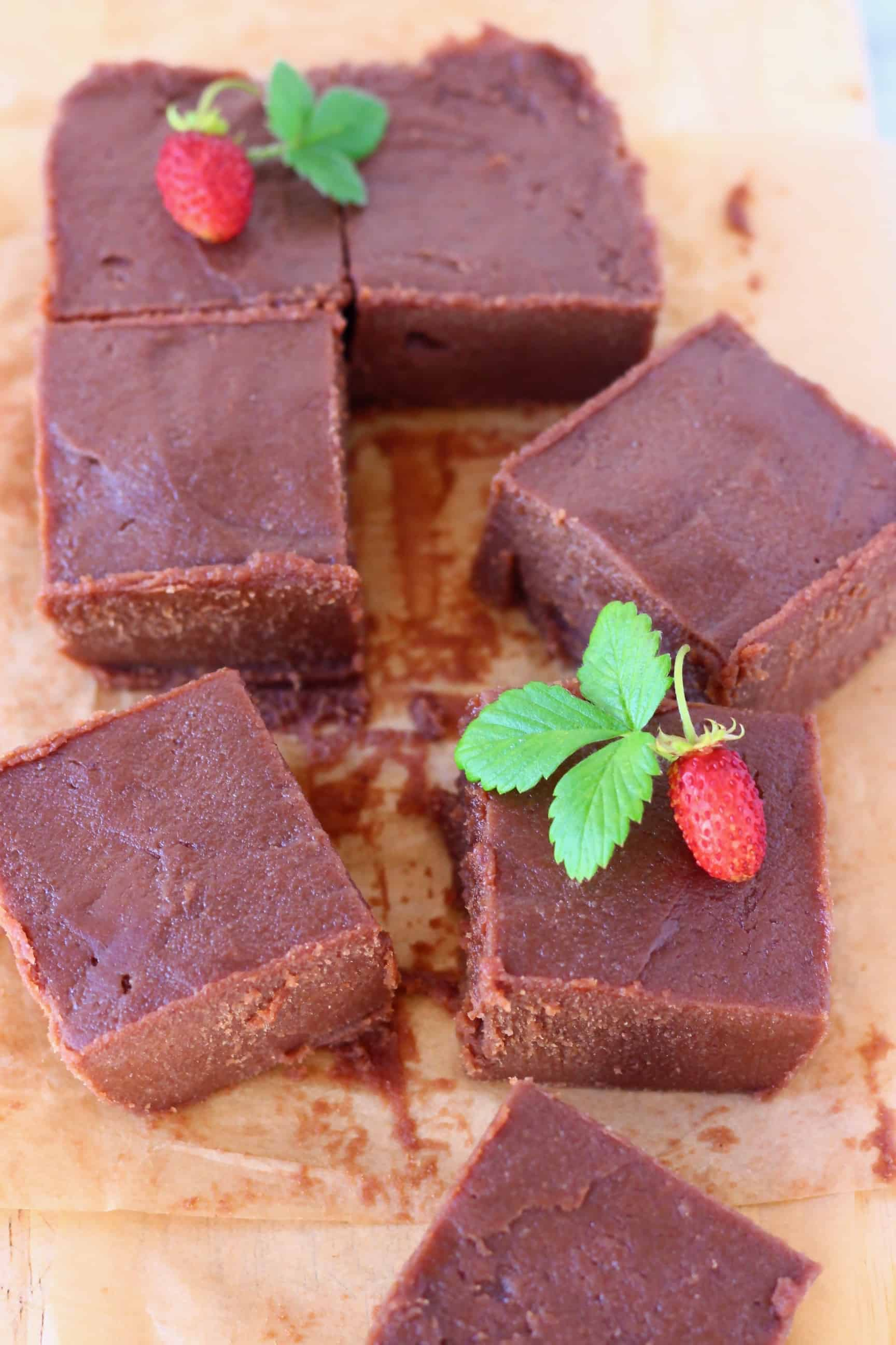 Seven square pieces of chocolate fudge on a sheet of brown baking paper decorated with mini strawberries with green leaves