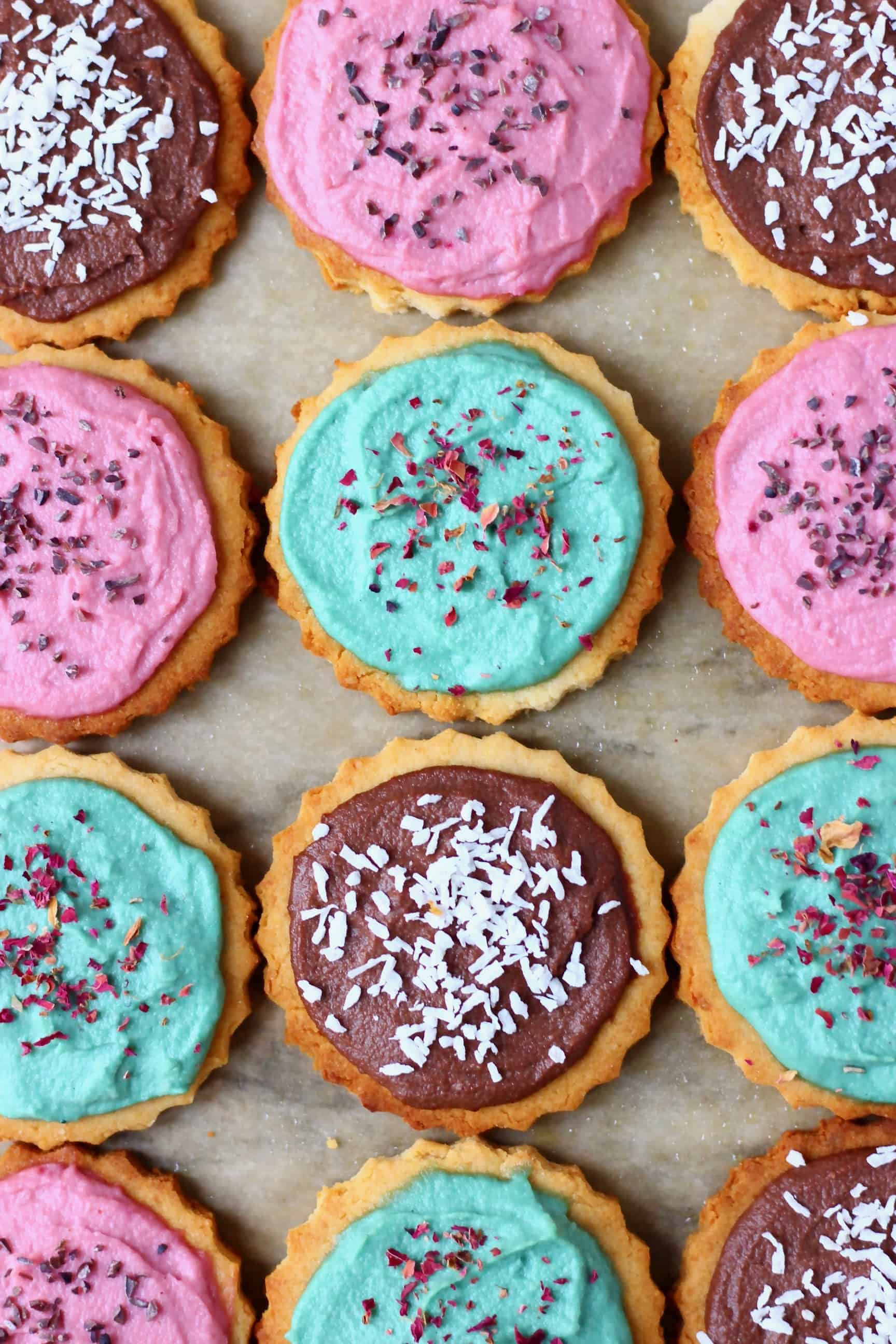 Twelve circular cookies topped with different coloured frosting and sprinkles on a sheet of brown baking paper
