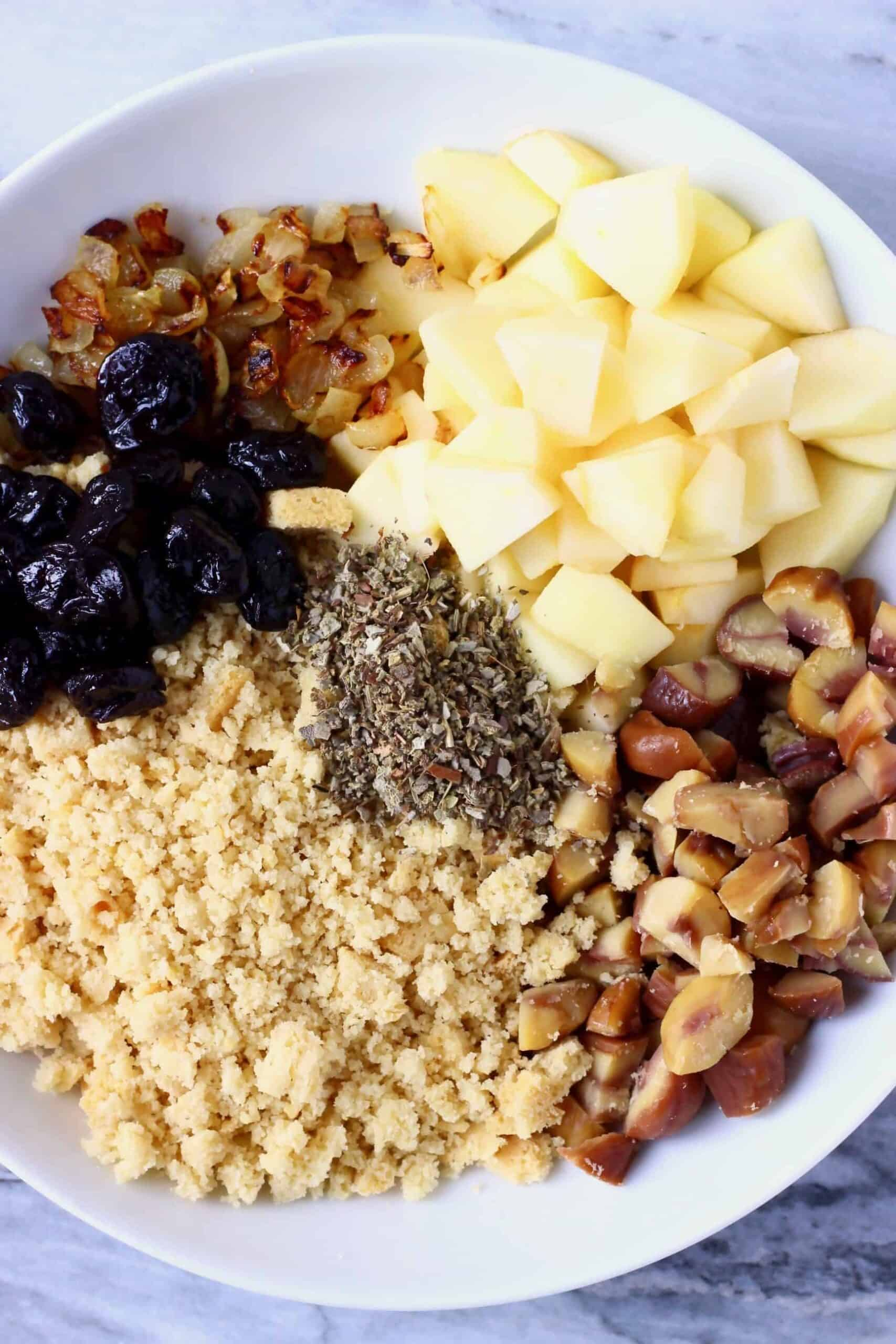 Diced apple, dried cherries, dried sage, chopped chestnuts, breadcrumbs and diced fried onion in a bowl