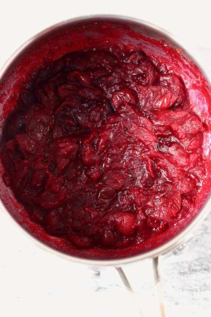 Photo of cranberry sauce in a silver saucepan against a marble background