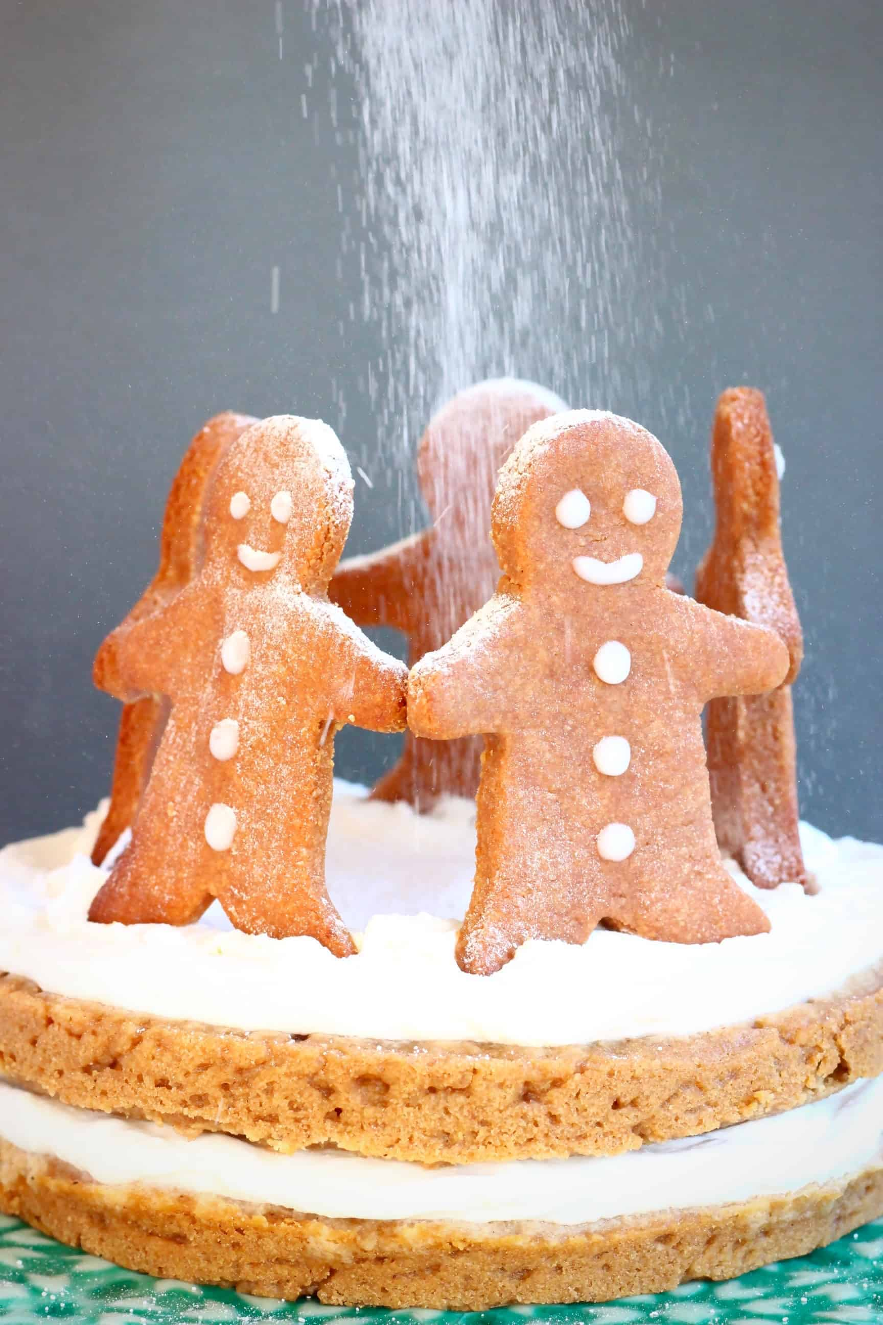 A gingerbread sponge cake sandwiched with white cream topped with five gingerbread men cookies standing in a circle with a dusting of white icing sugar