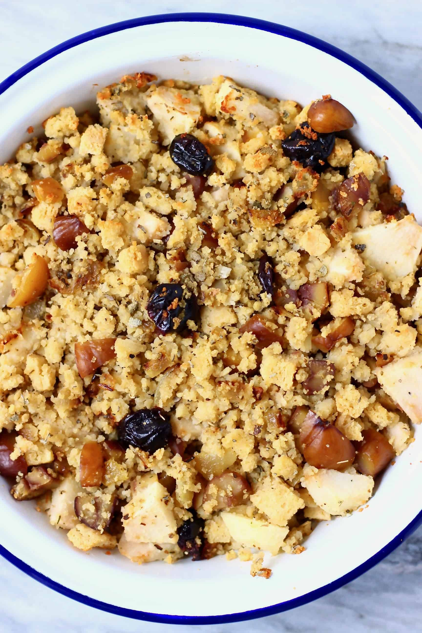 Diced apple, dried cherries, dried sage, chopped chestnuts, breadcrumbs and diced fried onion mixed together in a white pie dish with a blue rim