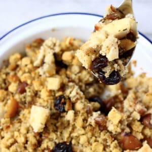 Gluten-free vegan stuffing with chestnuts, apple and dried cherries in a pie dish with a spoon holding up a mouthful