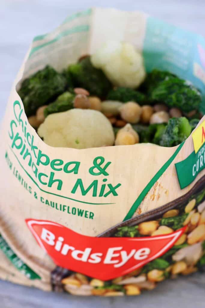 Photo of a bag of Birds eye Chickpea & Spinach Mix with the top open and frozen vegetables and beans inside