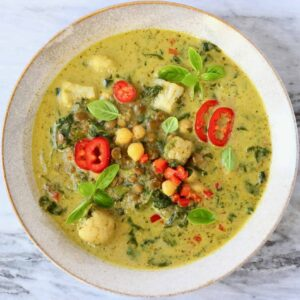 Photo of green curry with cauliflower, spinach, chickpeas and green lentils topped with basil and red chilli in a beige bowl against a marble background