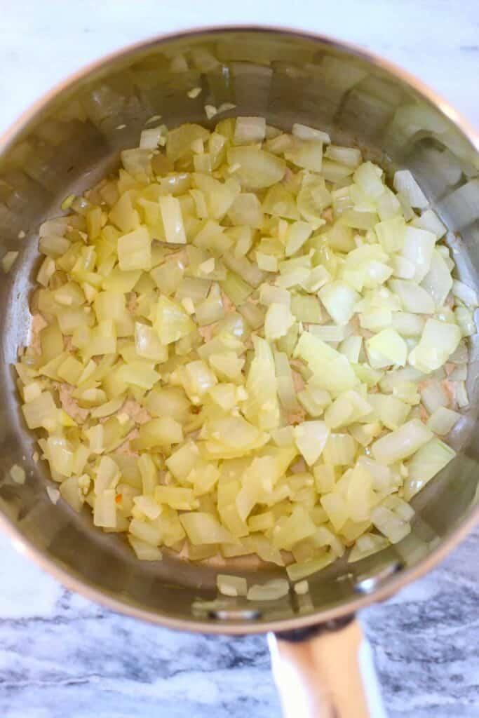 Photo of diced onion in a silver saucepan against a marble background