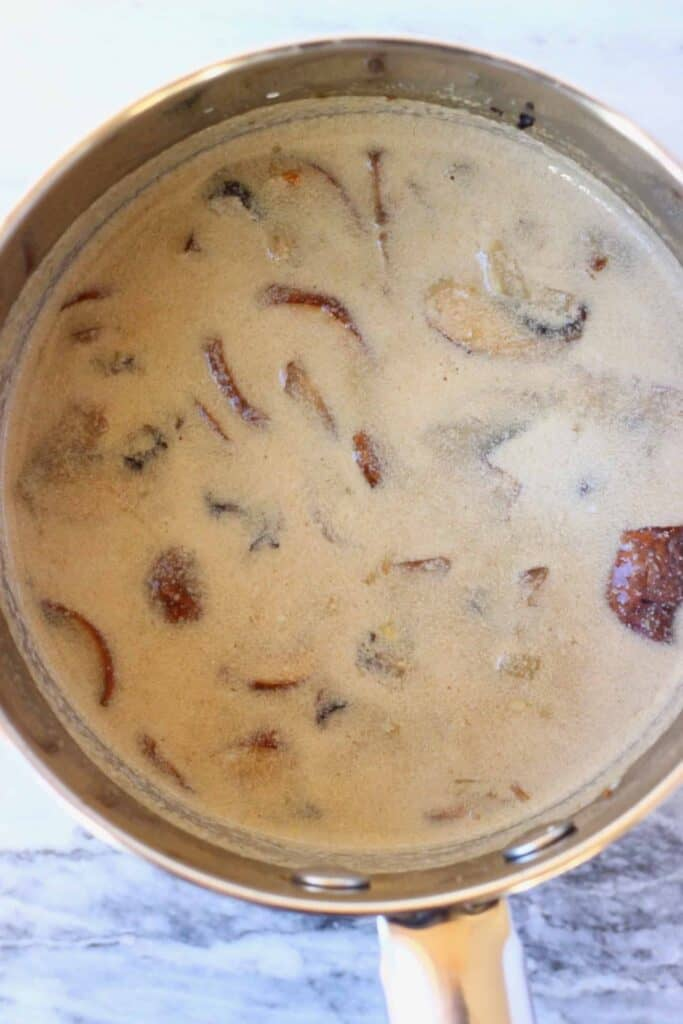 Photo of mushrooms in a brown creamy sauce in a silver saucepan against a marble background