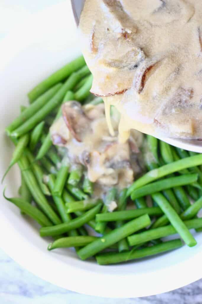 Photo of green beans in a white pie dish with a saucepan pouring over sliced mushrooms in a creamy brown sauce