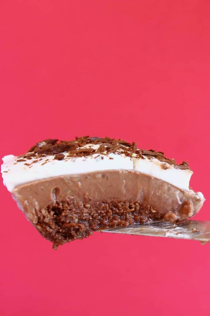 Photo of a slice of chocolate pie topped with whipped cream and chocolate shavings being held up against a bright pink background