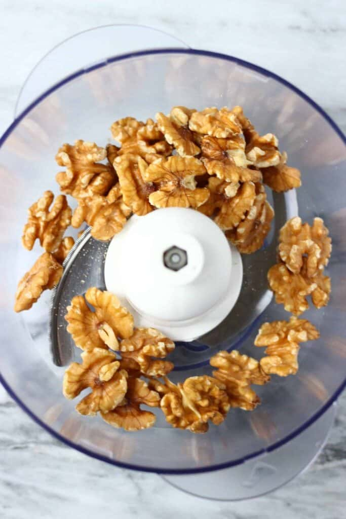 Walnuts in a food processor against a marble background
