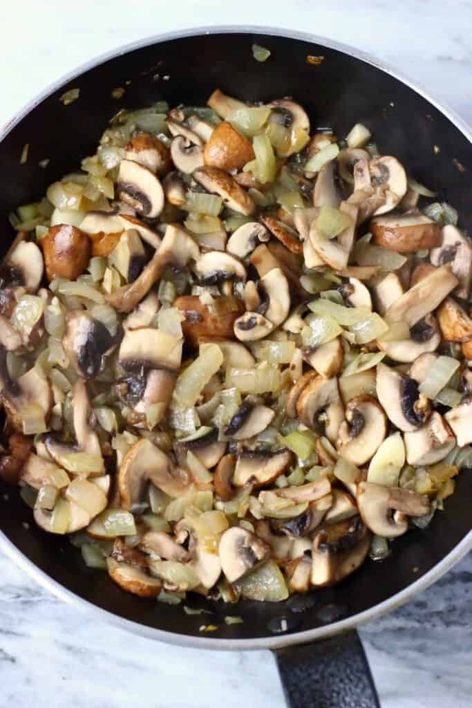 Diced onion and sliced mushrooms being fried in a black frying pan against a marble background