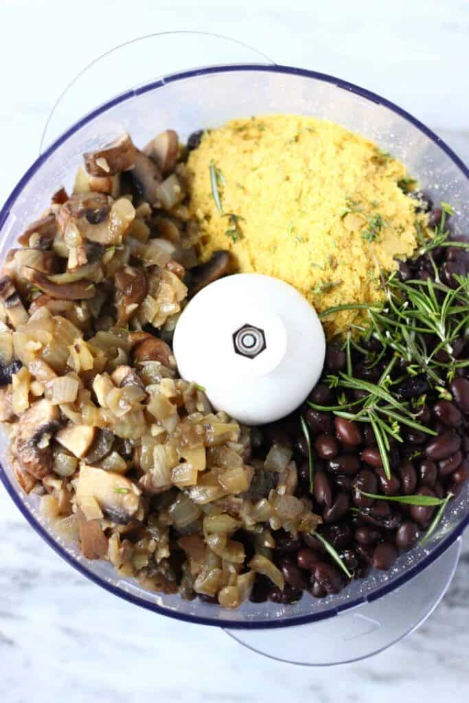 Fried onion and mushrooms, nutritional yeast, fresh rosemary, black beans and nutritional yeast in a food processor against a marble background