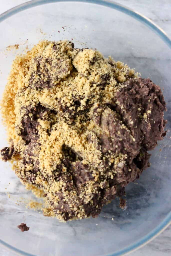 Black meatloaf mixture and ground walnuts in a glass mixing bowl against a marble background