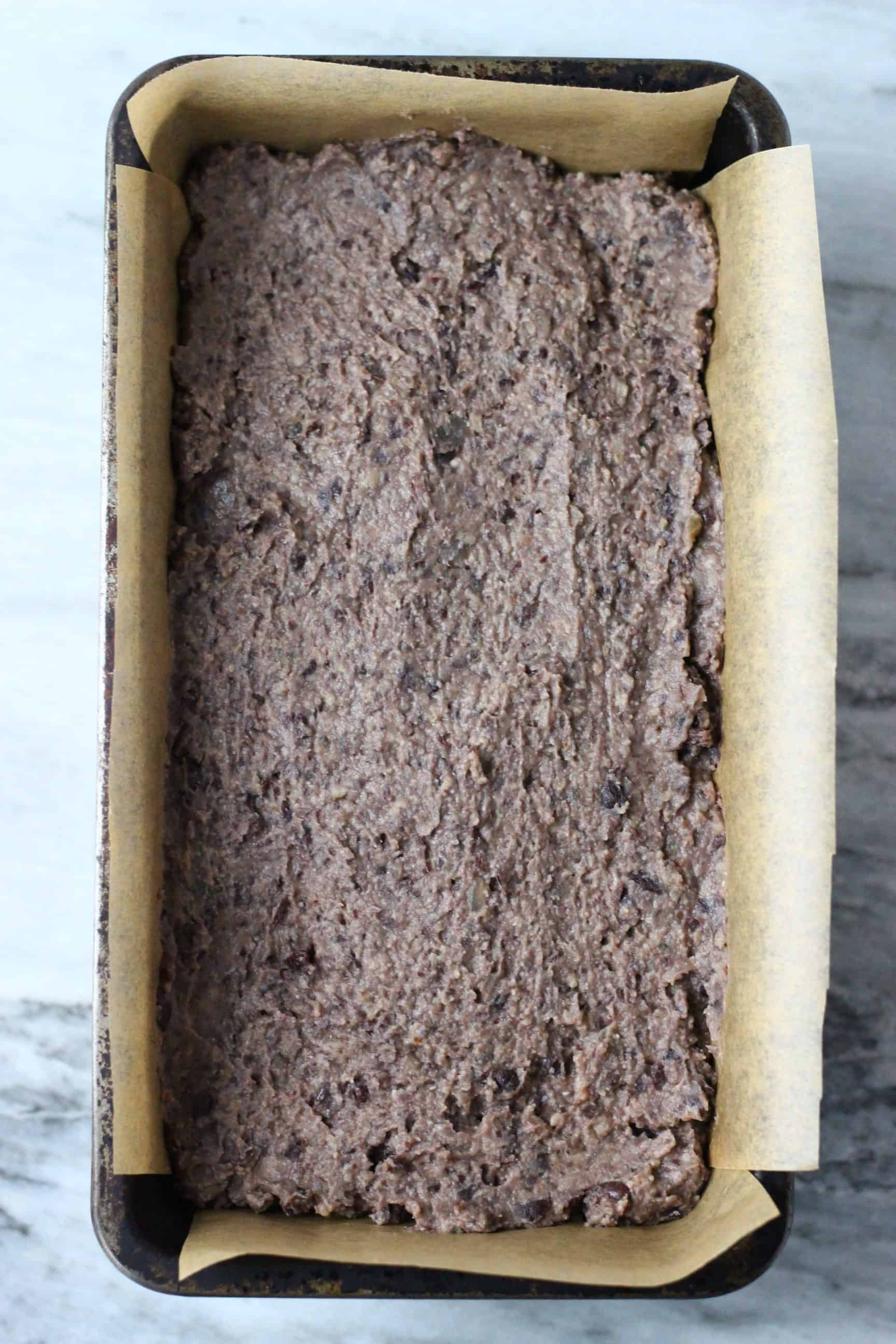 Vegan black bean meatloaf mixture in a loaf tin lined with baking paper